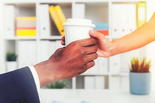 woman passing a man a coffee